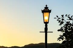 Posts de la lámpara del vintage con el fondo de la puesta del sol (sillhouette) Foto de archivo