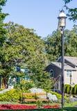 Posts de la lámpara por el banco en jardín Imagen de archivo