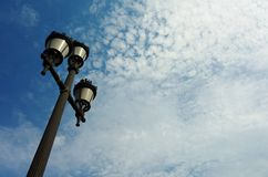 Posts de la lámpara y cielos azules nublados Foto de archivo
