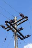 Posts eléctricos por el camino con los cables de la línea eléctrica, contra azul Imagen de archivo