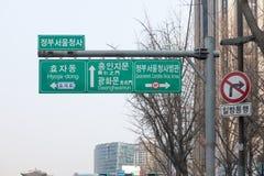 Posts múltiples de la señal de dirección con nombres de la ciudad en inglés y Kore Fotos de archivo libres de regalías