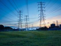 Posts o torre de alto voltaje del alto voltaje en campo verde en Butterworth, Penang, Malasia Imagenes de archivo