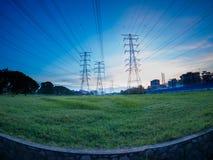 Posts o torre de alto voltaje del alto voltaje en campo verde en Butterworth, Penang, Malasia Fotografía de archivo