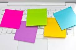 Posts pegajosos coloridos de las notas en el ordenador portátil blanco. fotografía de archivo
