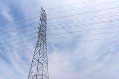 Posts y cable eléctricos de las telecomunicaciones del alambre con el fondo del cielo azul Foto de archivo libre de regalías