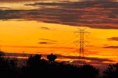 Posts y cielo de alto voltaje en el tiempo crepuscular Foto de archivo libre de regalías
