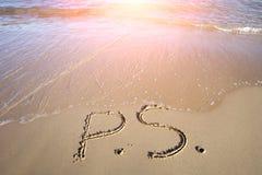 Postskriptum geschrieben auf nassen Sand Lizenzfreie Stockfotografie