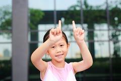 Postura asi?tica da menina que aponta seu dedo indicador acima com pouco sorriso fotografia de stock royalty free