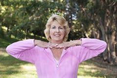 Postura practicante de la mujer mayor en parque Imagenes de archivo