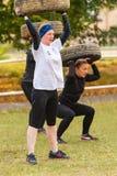 Posture accroupie de filles avec le pneu Photo stock