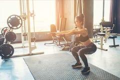 Posture accroupie profonde de jeune belle femme dans les vêtements de sport faisant le wh accroupi Photos stock