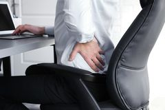 Posture concept. Man suffering from back pain while. Working with laptop at office stock image