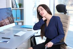 Posture concept. Young woman suffering. From neck pain while working with computer at office royalty free stock photos
