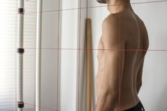 Posture and equilibrium analysis of body growth. Orthopedic physiotherapist check body growth of young athlete stock photo