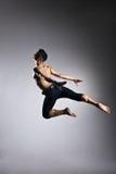 Posture gymnastique de saut d'homme caucasien sur le gris photos libres de droits