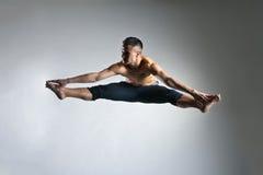 Posture gymnastique de saut d'homme caucasien sur le gris image stock