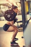 Postures accroupies avec le barbell au centre de fitness photographie stock