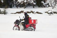 Postzustellung im Schnee auf einem Motorrad Stockfotografie