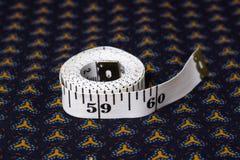 Posuwa się wolno, centymetrowa taśma na tle błękitna tkanina z patt Zdjęcie Royalty Free