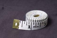 Posuwa się wolno, centymetrowa taśma na tle popielata tkanina Obraz Royalty Free