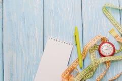Posuwa się wolno krawczyny z notatnikiem i stopwatch na błękitnym tle Fotografia Stock