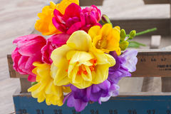 Posy  of spring flowers on wooden table. Fresh posy  of pink tulips,  yellow daffodils and freesea flowers on wooden table Royalty Free Stock Images