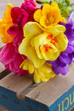 Posy  of spring flowers on wooden table. Fresh posy  of pink tulips,  yellow daffodils and freesea on wooden table Royalty Free Stock Image
