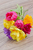 Posy  of spring flowers on wooden table. Posy  of pink tulips,  yellow daffodils and freesea flowers on wooden table Stock Image