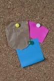 Poszarpana brown papierowa torba na corkboard z kolorowymi notatkami i szpilkami dołączającymi. fotografia royalty free