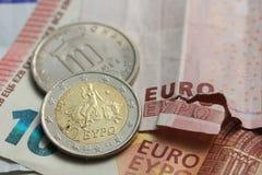 Poszarpana euro notatki i rocznika grka moneta Zdjęcie Stock
