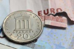 Poszarpana euro notatki i rocznika grka moneta Zdjęcia Stock