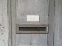 Poszarpane i stronniczo exfoliated warstwy farba na starym drewnianym drzwi z jasnymi pęknięciami, skrzynki pocztowej szczelina obrazy royalty free