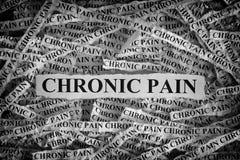 Poszarpani kawałki papieru z słowo Chronicznym bólem zdjęcie stock