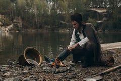 Poszukiwacza złota warmin w górę pobliskiego ogienia na skalistym banku Zdjęcia Stock