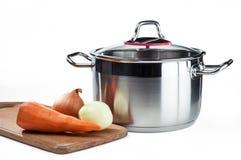 Pot à cuire inoxydable avec des légumes sur une planche à découper images stock
