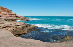 Pot Alley. Turquoise Indian Ocean seascape and red sandstone cliffs with the natural recess on the Pot Alley gorge coast line under clear blue skies in Kalbarri Royalty Free Stock Photos