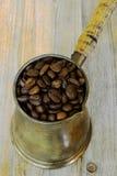 Pot arabe de café sur le fond en bois avec des haricots Images stock