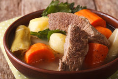 Pot-au-feu beef soup with vegetables in a bowl macro. horizontal. Pot-au-feu beef soup with vegetables in a bowl macro on the table. horizontal Stock Images