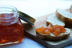 Pot avec de la confiture de pomme et la tranche faites maison de pain de seigle sur un plan rapproché de conseil en bois Photo stock