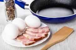 Pot avec le condiment, poêle, oeufs crus, poitrine dans le plat, spatule sur la table en bois photos libres de droits