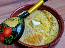 Pot avec le gruau de millet du four Gruau des céréales de millet sur le lait, beurre Cuillère de Khokhloma closeup rétro Images libres de droits