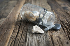 Pot of beach on the table. Glass pot of rocks from the beach on a wooden table.Souvenir Stock Images