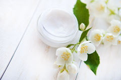 Pot of beauty cream with flower petals on white wooden table Royalty Free Stock Photo