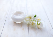 Pot of beauty cream surrounded by flowers on white wooden table Royalty Free Stock Photo