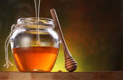Pot is being filled with honey and a drizzler. Stock Photography