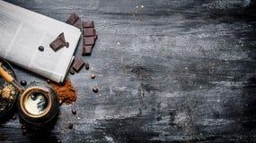 Pot brassé de café avec le journal frais et le chocolat amer Images stock