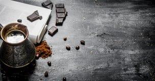 Pot brassé de café avec le journal frais et le chocolat amer Photographie stock