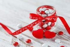 Pot coloré de sucrerie décoré d'un arc rouge avec des coeurs sur le fond en bois blanc Concept de jour de Valentines Image libre de droits