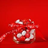Pot coloré de sucrerie décoré d'un arc rouge avec des coeurs sur le fond rouge Concept de jour de Valentines Photos stock