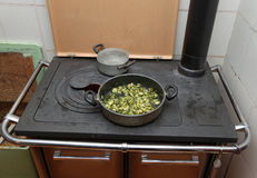 Pot with cooked zucchini in the ancient stove with fire lit Royalty Free Stock Photos